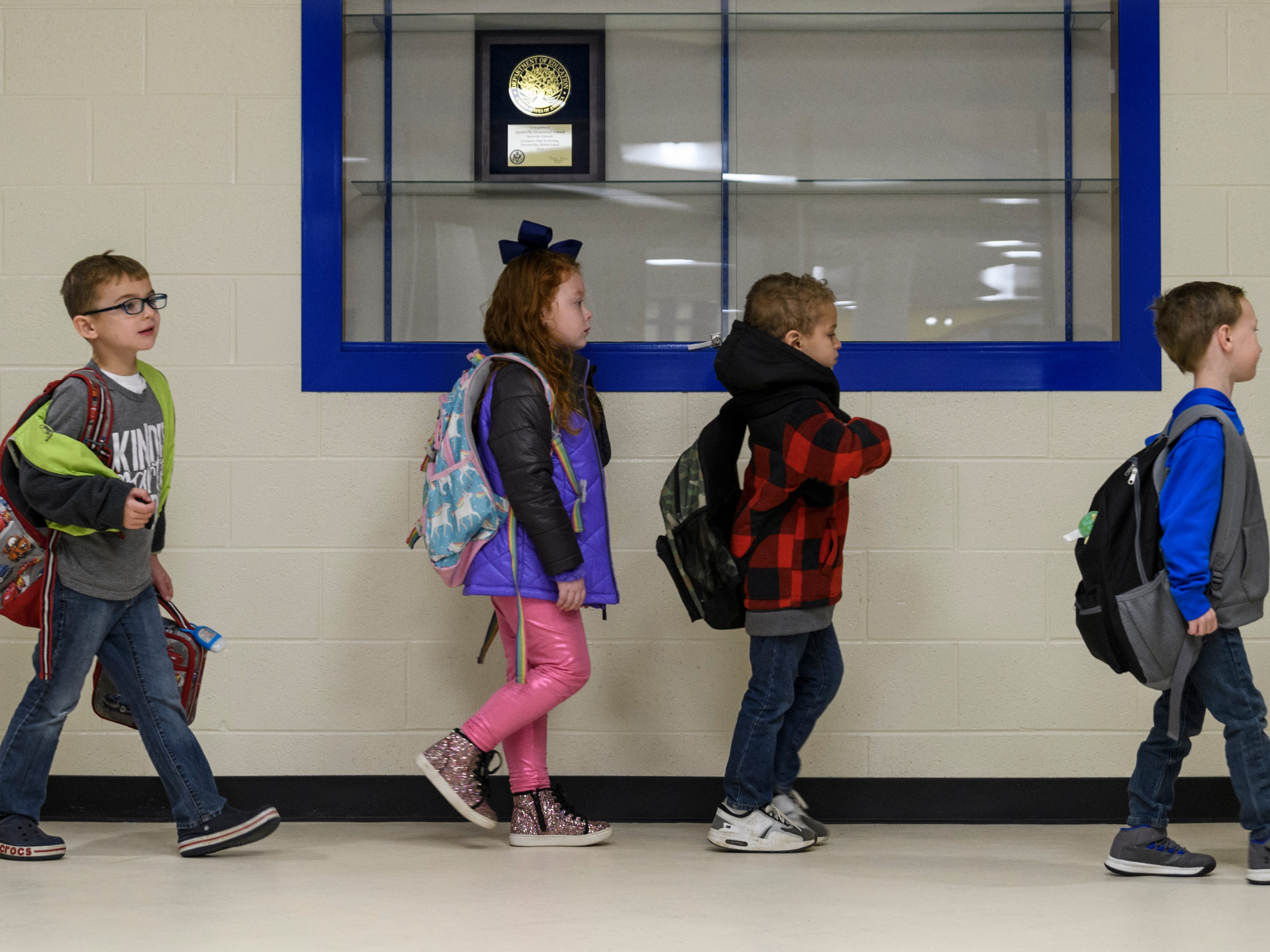 Students walk to their classrooms, past the awards case that holds a 2018 National Blue Ribbon School plaque,  during the first school day inside the new Spottsville Elementary School building, Monday morning, Nov. 12, 2018.