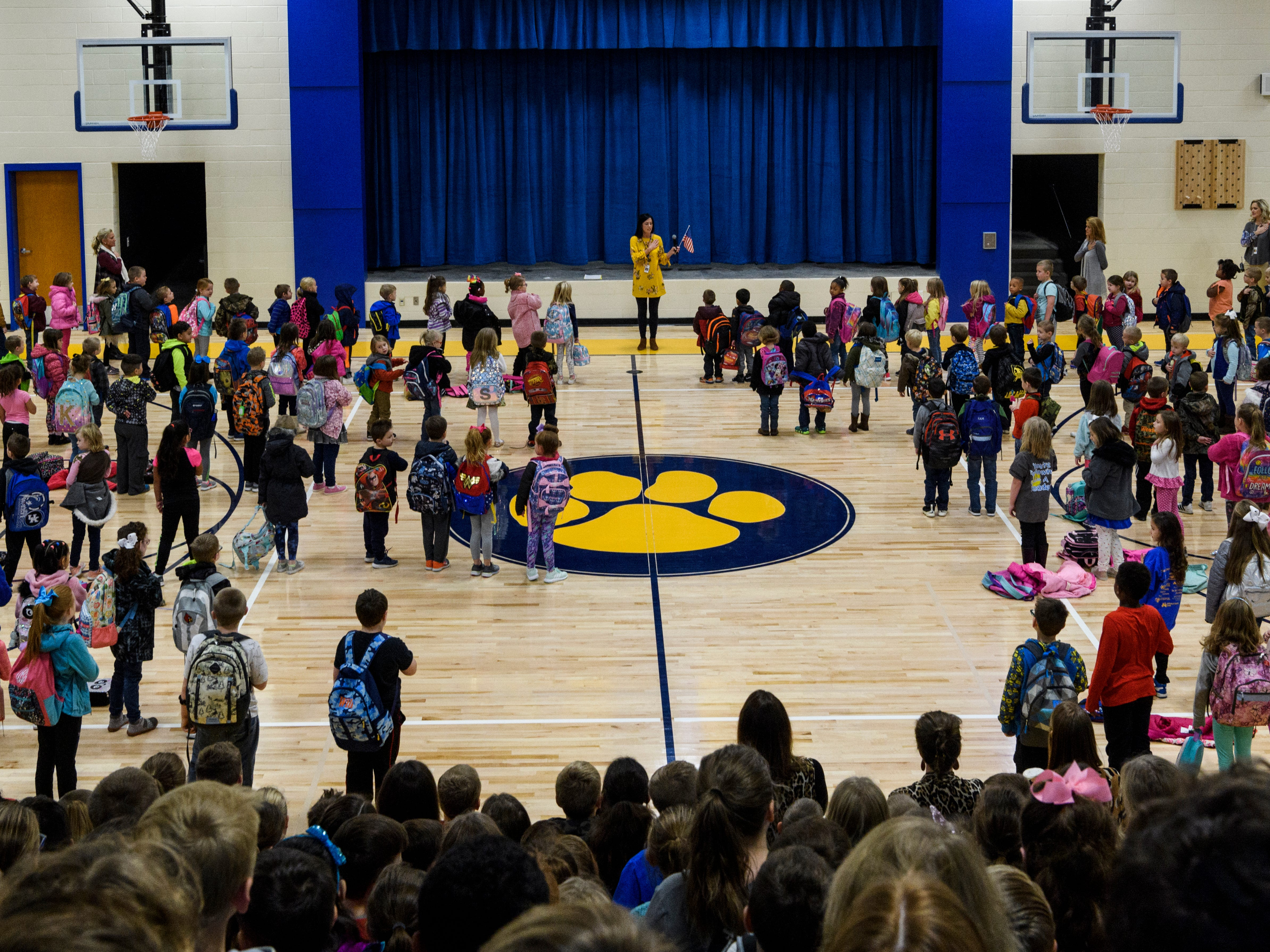 """Principal Sarah Estabrook, top center, leads the """"Pledge of Allegiance"""" during the morning assembly inside the gymnasium at Spottsville Elementary school, Monday, Nov. 12, 2018. Monday was the first time that students had school inside the new $17 million, 76,796 square-foot facility."""