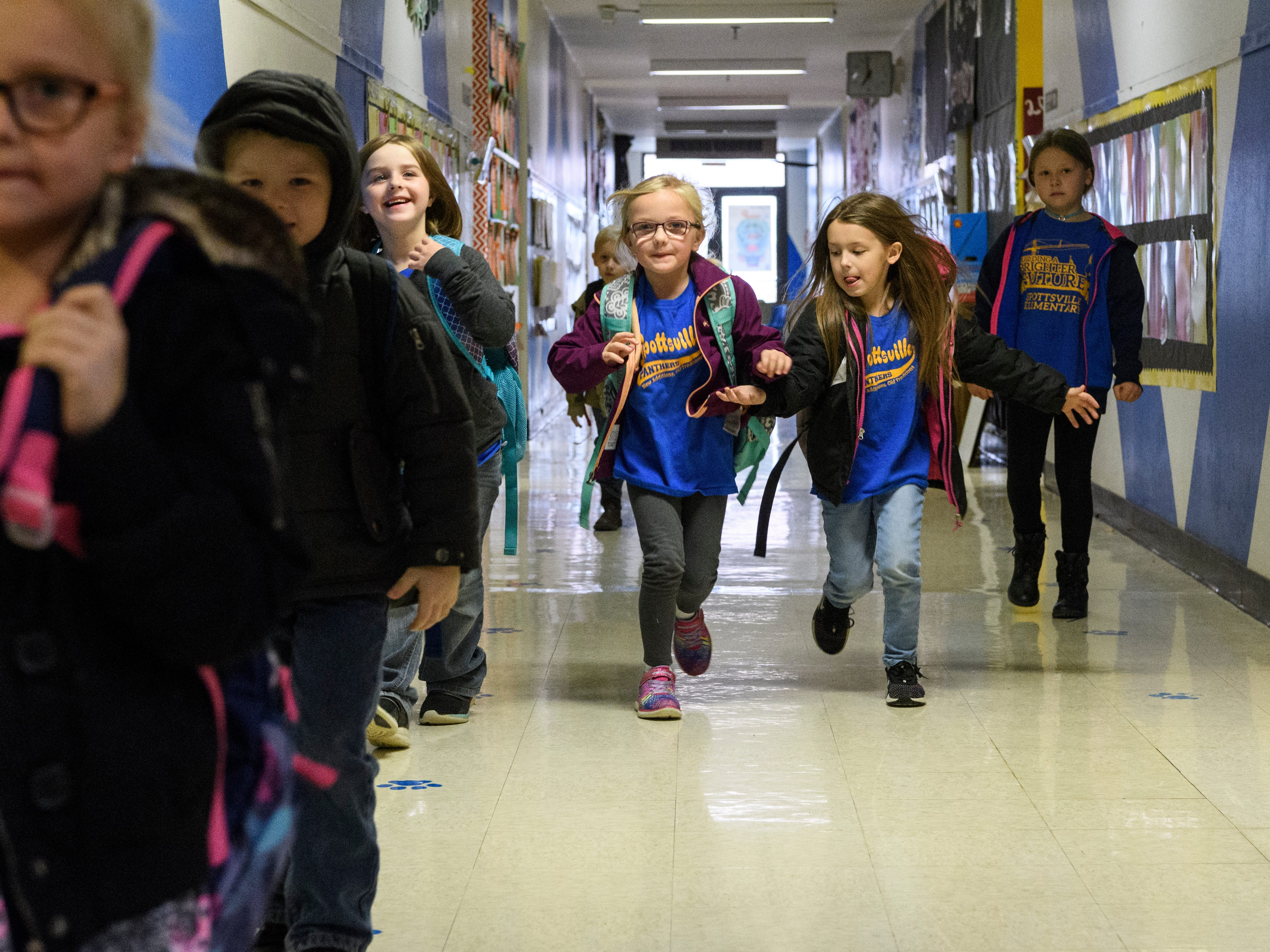 Kindergarteners Addyson O'Nan, center left, and Grace Ruark, center right, run down the hallway of Henderson's Spottsville Elementary school one last time after being dismissed from Denise Cannon's class, Friday morning, Nov. 9, 2018. The students moved into the new school building,  located right beside the old one, Monday morning, November 12, 2018.