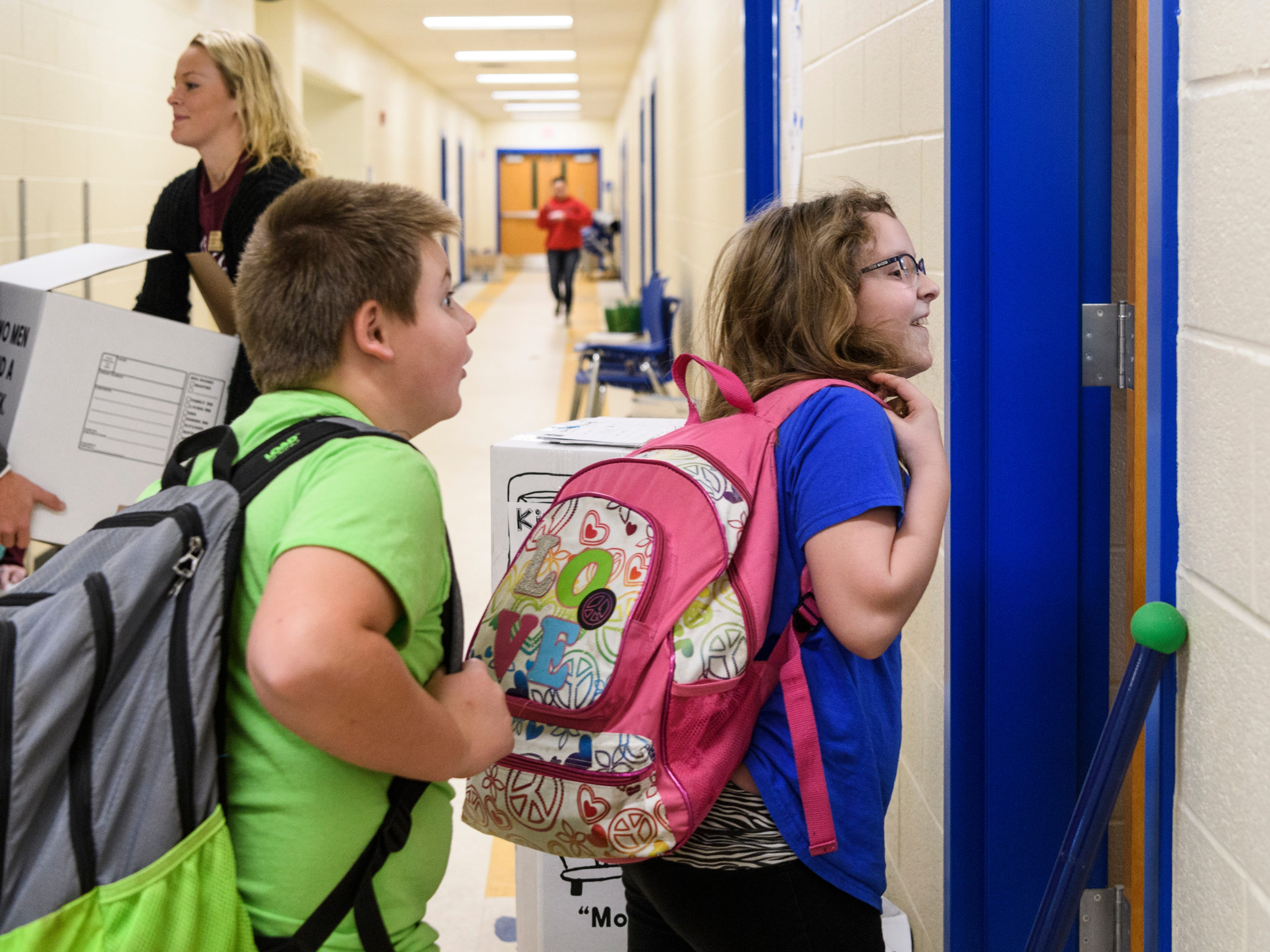 Alex Roberts, left, and Lindsay Payne, right, walk into their fourth-grade teacher Katie Kirkwood's classroom during a sneak peak tour of the new Spottsville Elementary school building, Friday morning, Nov. 9, 2018. The students used part of their early dismissal day to move items over from the old building in preparation for the scheduled move-in on Monday, Nov. 12.