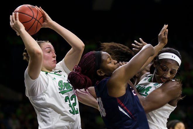 Notre Dame's Jessica Shepard (32) grabs a rebound next to teammate Jackie Young, right, and Pennsylvania's Princess Aghayere (50) during the first half of an NCAA college basketball game Monday, Nov. 12, 2018, in South Bend, Ind.