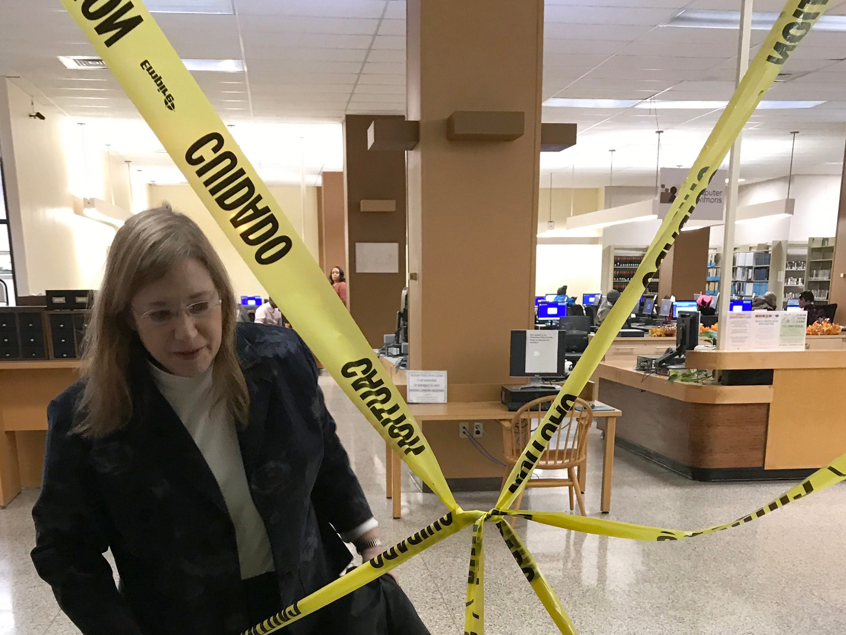 Hinds County Library System director Patty Furr pulls caution tape away from a stairwell doorway in the Eudora Welty branch of Jackson. The tape is meant to keep patrons away from upper floors damaged by the continued assault of leaking rain water and subsequent mold. Tuesday, Nov.13, 2018.