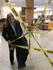 Hinds County Library System Director Patty Furr pulls caution tape away from a stairwell doorway in the Eudora Welty branch of Jackson on Nov.13, 2018. The tape is meant to keep patrons away from the upper floor, damaged by the continued assault of leaking rainwater and subsequent mold.