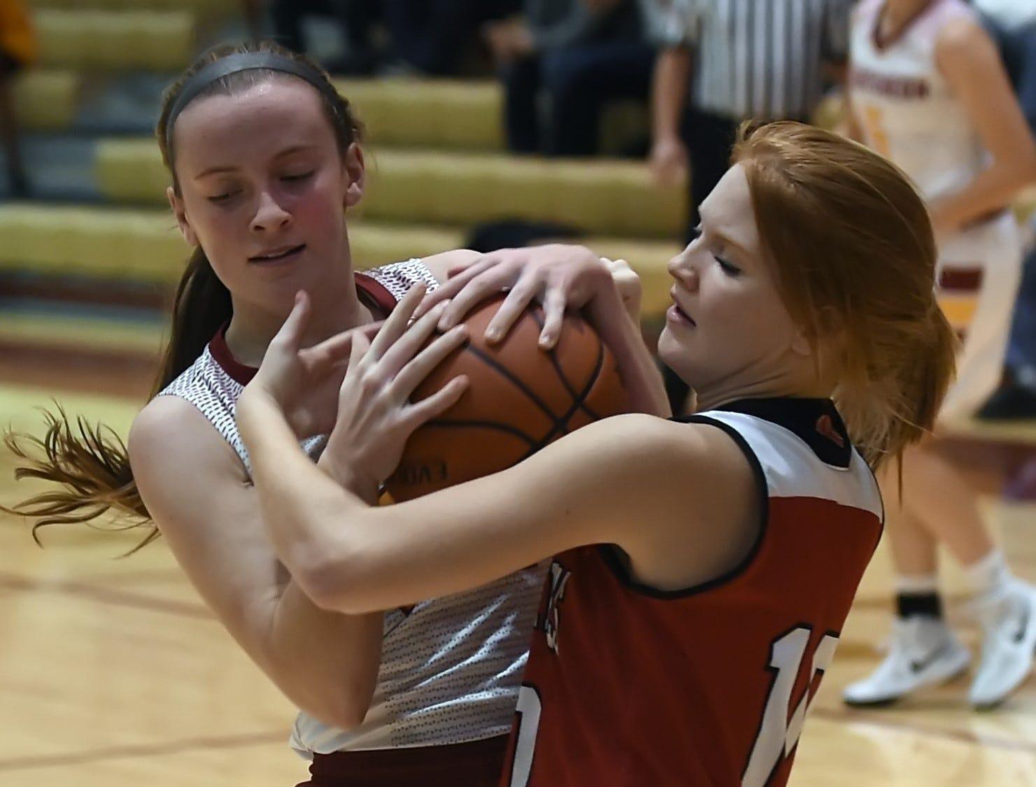 Junior McCutcheon guard Bailey Burton tangles with Twin Lake's Kayla Bennington for control of a rebound.