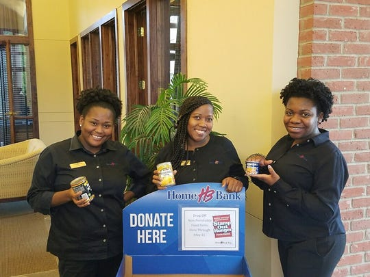 Home Bank staff in Baton Rouge collect canned goods for the Stamp Out Hunger food drive.