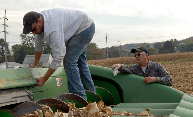 Tim Claypool, right, has Emerson Martin adjust a tarp on a combine corn head in this Oct. 13, 2011, file photograph at Claypool Farms in Hocking Township. Claypool, a Hocking Township Trustee, died over the weekend.Gazette