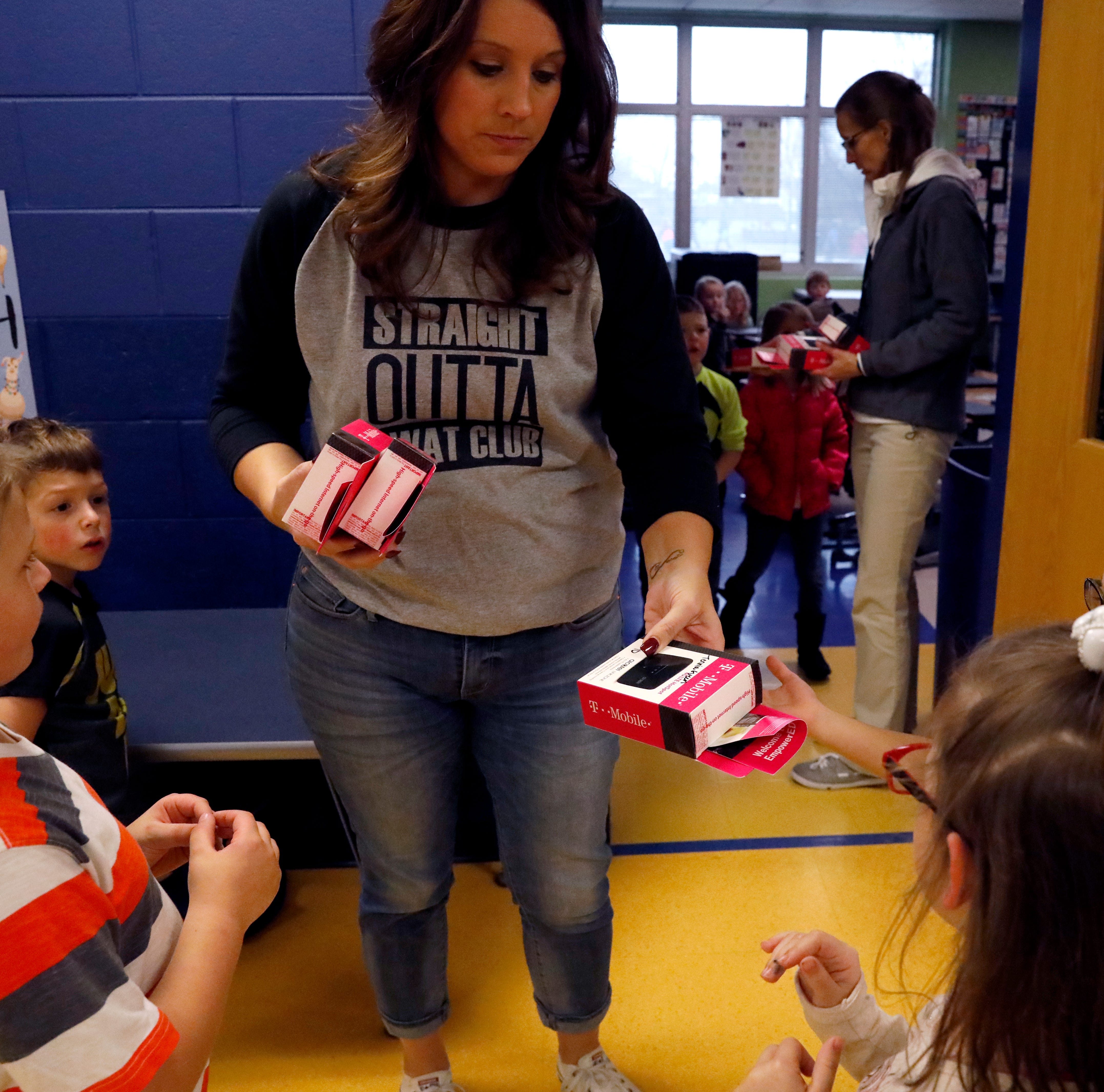 JoLena Sark, a first grade student at Gorsuch West Elementary hands out mobile Wi-Fi hotspot devices to some of her students Tuesday afternoon, Nov. 13, 2018, in Lancaster. A grant from T-Mobile allowed the district to distribute the devices to every high school student and to students at Gosuch West and Tallmadge Elementary who's parents agreed to receive the devices. The two year grant allows those with the device to have free access to the internet.