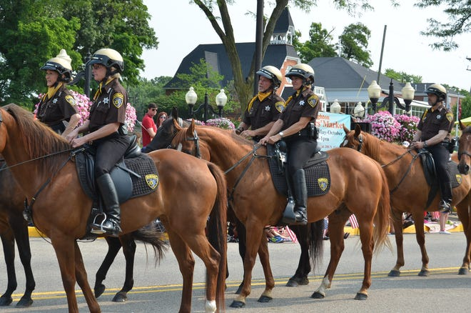 Livingston County Mounted Patrol Deputies participate in a parade along Main Street in Brighton.