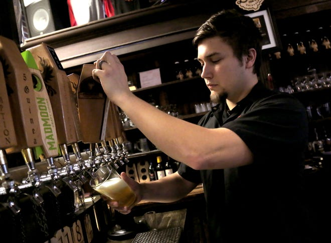 Ian Caldwell, a brewer at Phoenix Brewery, pours out the new Turbidity New England IPA.