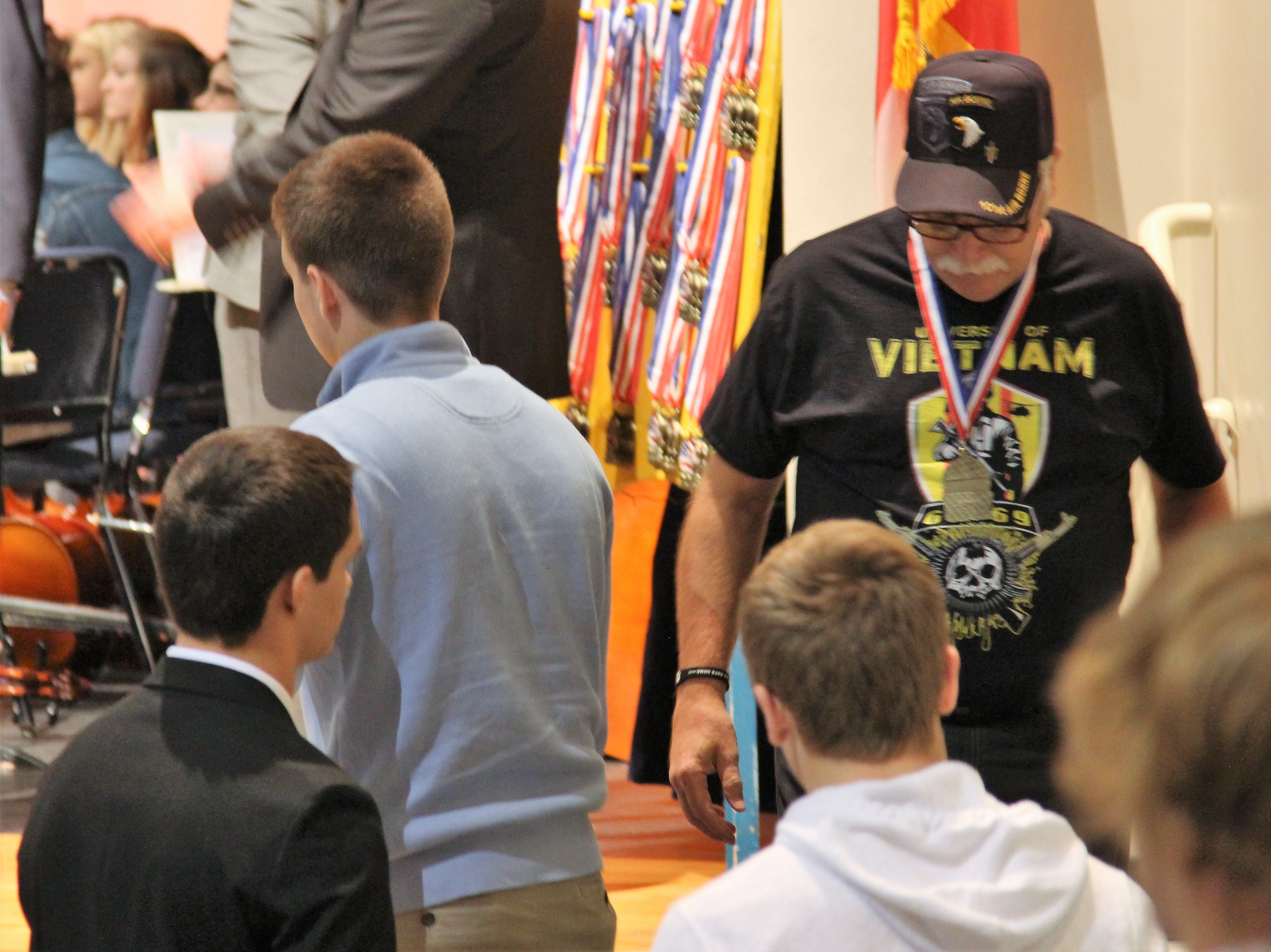 A Vietnam veteran walks back to his seat on Tuesday with a medal hanging from his neck. Students at River Valley High School honored Marion County veterans with medals and speeches following Veterans Day.