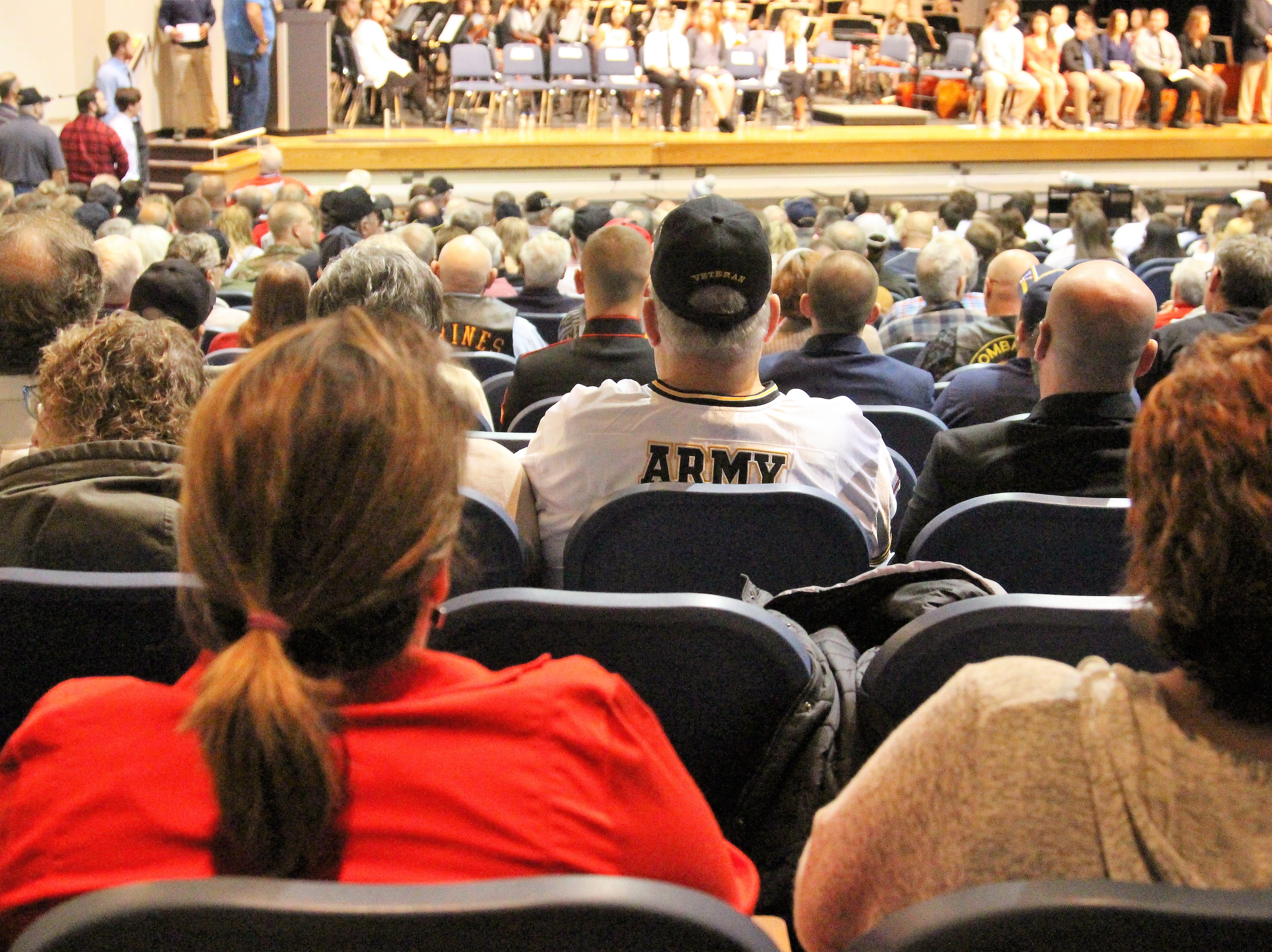 An Army veteran listens to River Valley students give speeches and present medals to loved ones during a post Veterans Day celebration.
