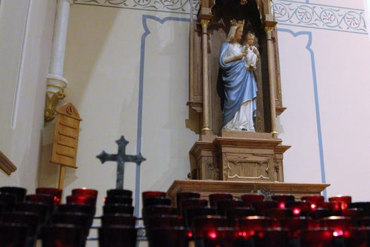 Members of the parish lit candles and whispered prayers as a statue of the Virgin Mary looked upon them. Carved wood was added to the sanctuary as a part of a beautification project that started earlier this year.
