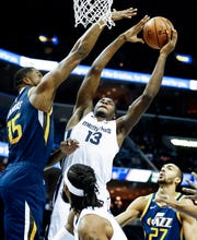 Memphis Grizzlies forward Jaren Jackson Jr. (middle) goes up for a put back layup against Utah Jazz defenders Derrick Favors (left) and Rudy Gobert (right) during action at the FedExForum in Memphis, Tenn., Monday, November 12, 2018.