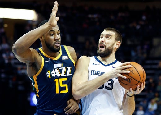 Memphis Grizzlies center Marc Gasol (right) drives the lane against Utah Jazz defender Derrick Favors (left) during  action at the FedExForum in Memphis, Tenn., Monday, November 12, 2018.