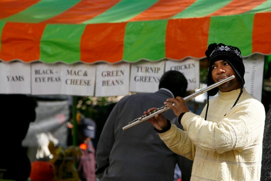Memphian Gregory Vassar, who performs under the name Jerome, plays some music for COGIC Holy Convocation attendees in November 2007 buying lunch from street vendors along Main Street.