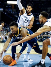 Memphis Grizzlies teammeats Garrett Temple (left) and Kyle Anderson (right) apply defensive pressure to Utah Jazz guard Donovan Mitchell (middle) during action at the FedExForum in Memphis, Tenn., Monday, November 12, 2018.