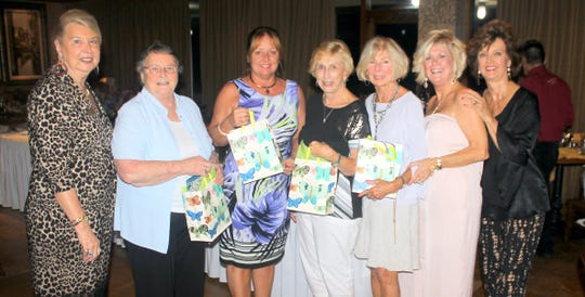 Just Friends president Rachel DeHanas and event co-chair Sharon Cook and Candy Seward present door prizes to Karen Hewitt, Sharon Walklett, Madeline Moore and Susanne Grossman
