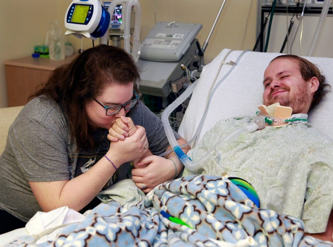 Bridget Spoerri kisses the hand of her husband Adam who contracted acute flaccid myelitis two weeks after their wedding. He is being treated at Post Acute Medical Specialty Hospital  in Greenfield.