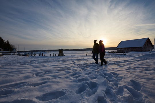 A couple enjoys a sunset hike at Ephraim's Anderson Dock in winter.