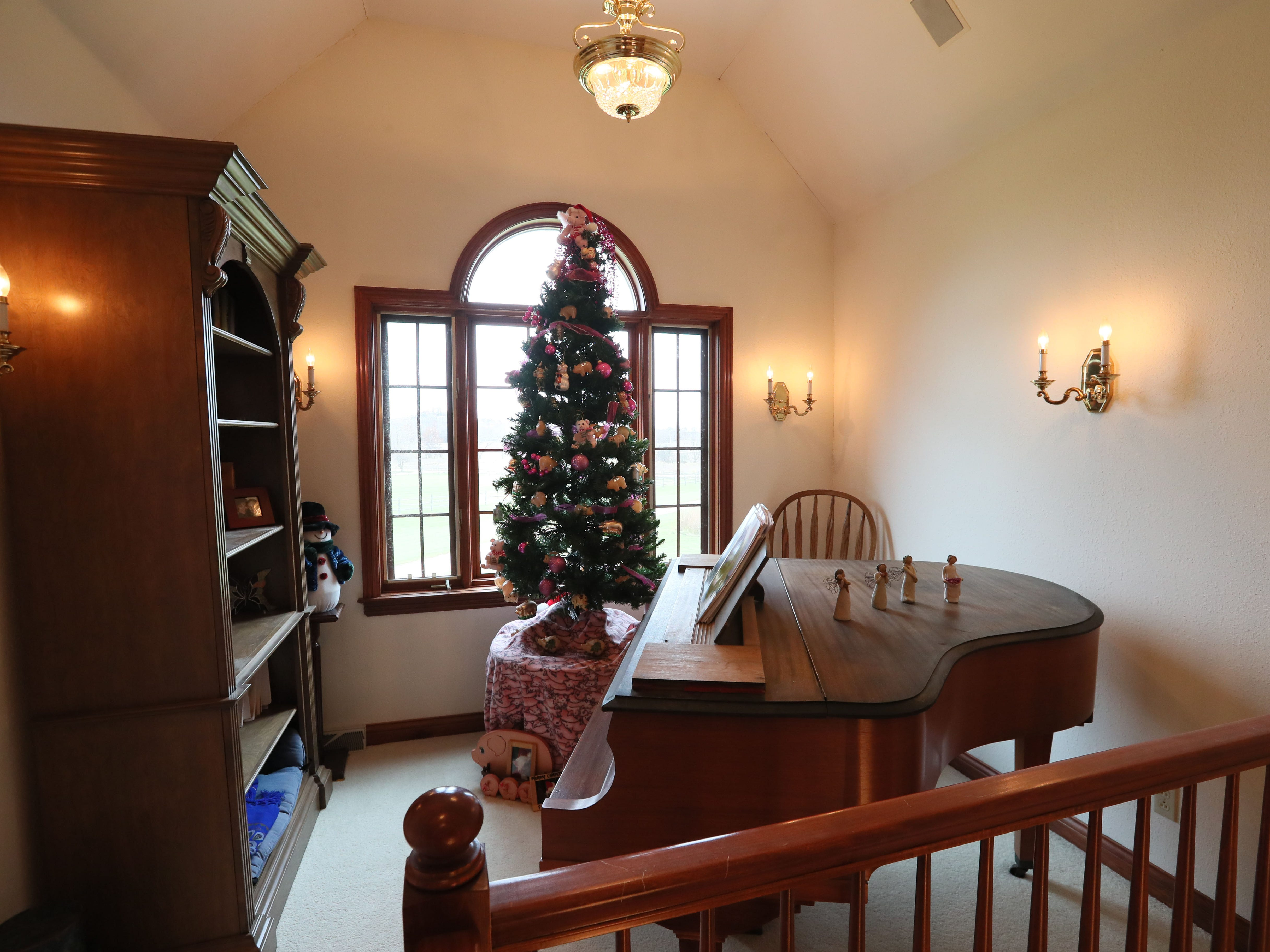 An area at the top of the stairs features a grand piano and a tabletop Christmas tree.