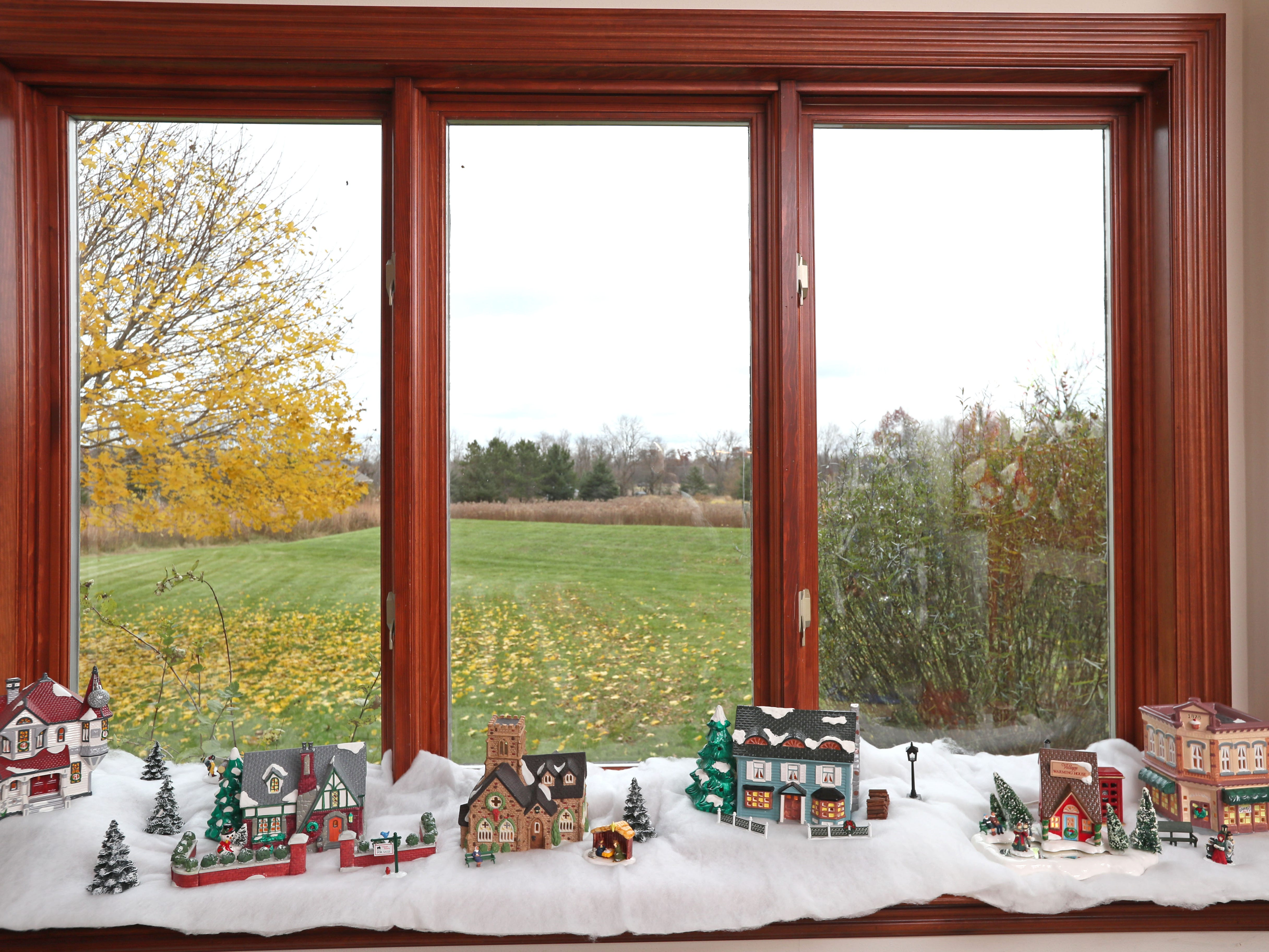 A winter Christmas village scene sits on a window ledge in the family room.