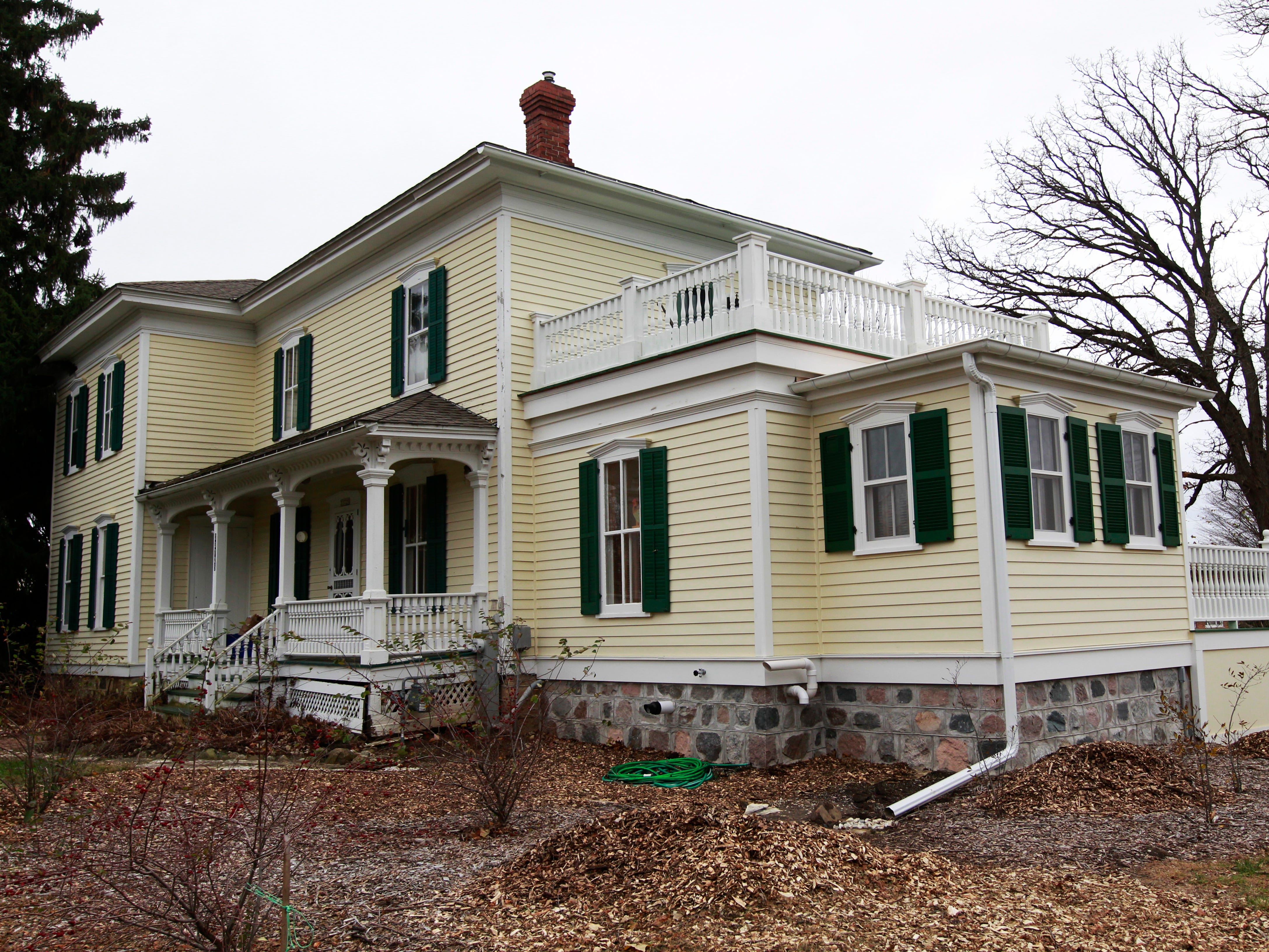 One of two additions to the Italianate farmhouse is to the right of the front porch.