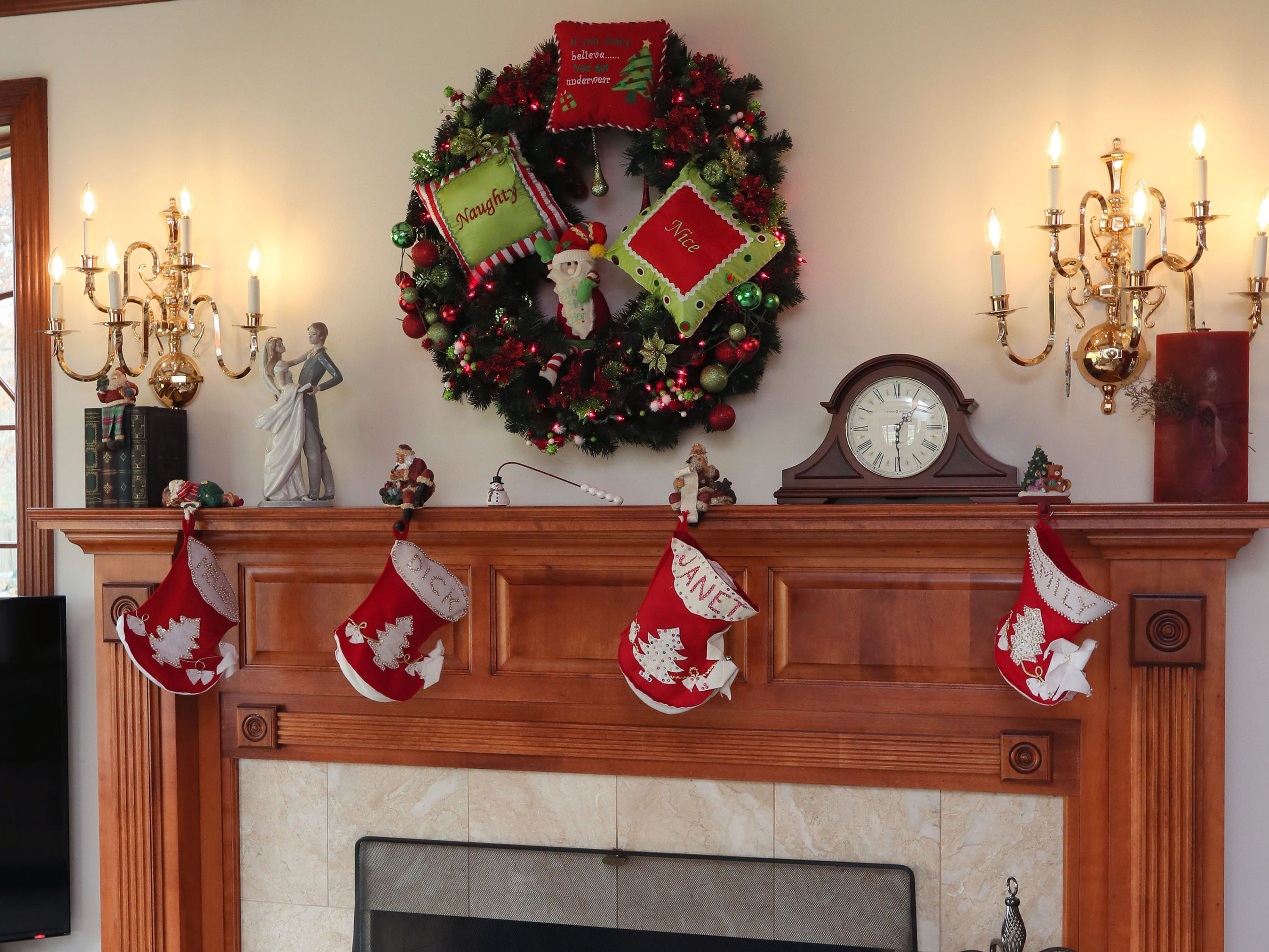 The family room fireplace is simply decorated with a large wreath and family members' stockings.