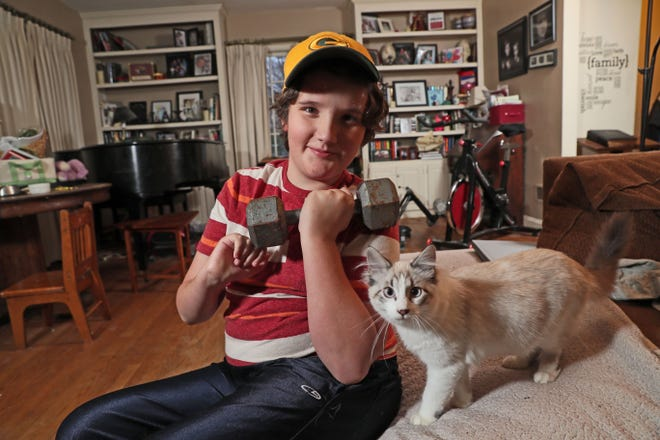 August McNall, 10, of Janesville survived a case of acute flaccid myelitis. He is using a weight to build strength in his left arm.