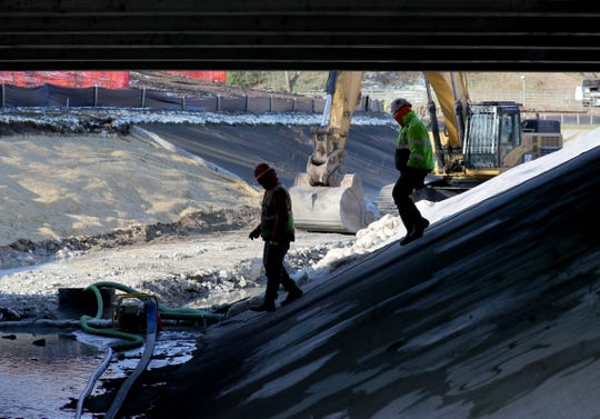Workers with C.W. Purpero Inc. of Oak Creek check a pump draining water from the bed of the Kinnickinnic River at South Sixteenth Street in Pulaski Park. The crew is removing concrete (rear) lining the river bed in the park as part of a flood-control plan for the river and its tributaries.
