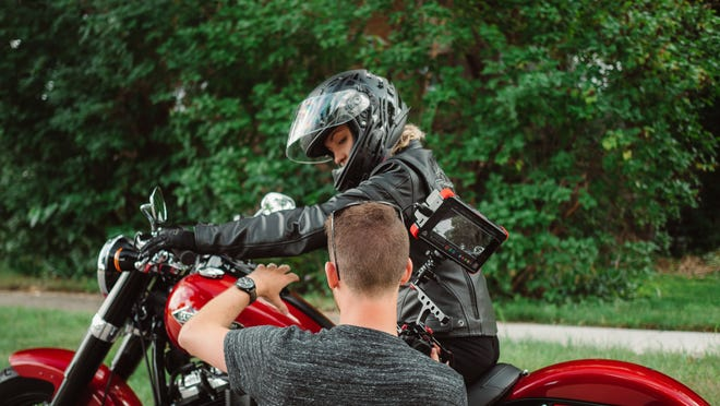 Alex Bellville sets up a camera and monitor to film Tessa Otto for a 60-second video about Otto's internship with Harley-Davidson.