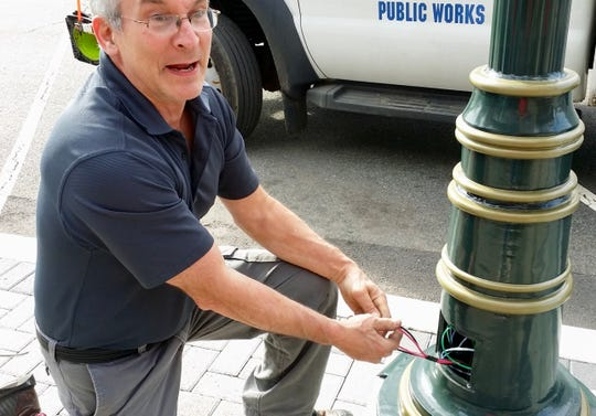 Denville Township Facilities Manager John Ciardi readies a street lamp for the new downtown speaker system.