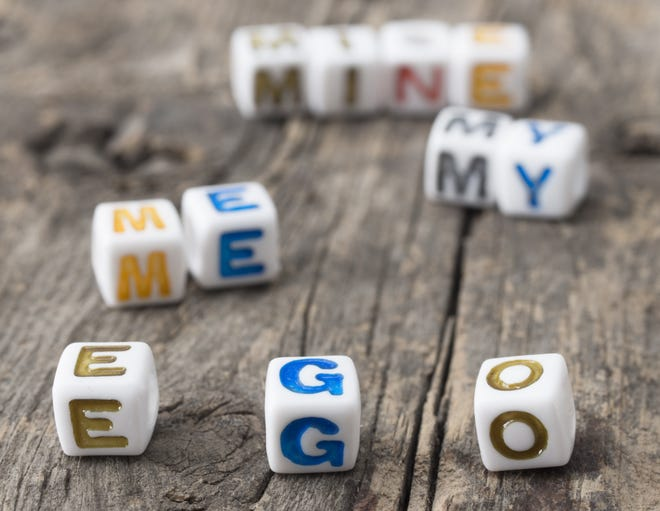 Letters on cubes spelling ego, me, my, mine.