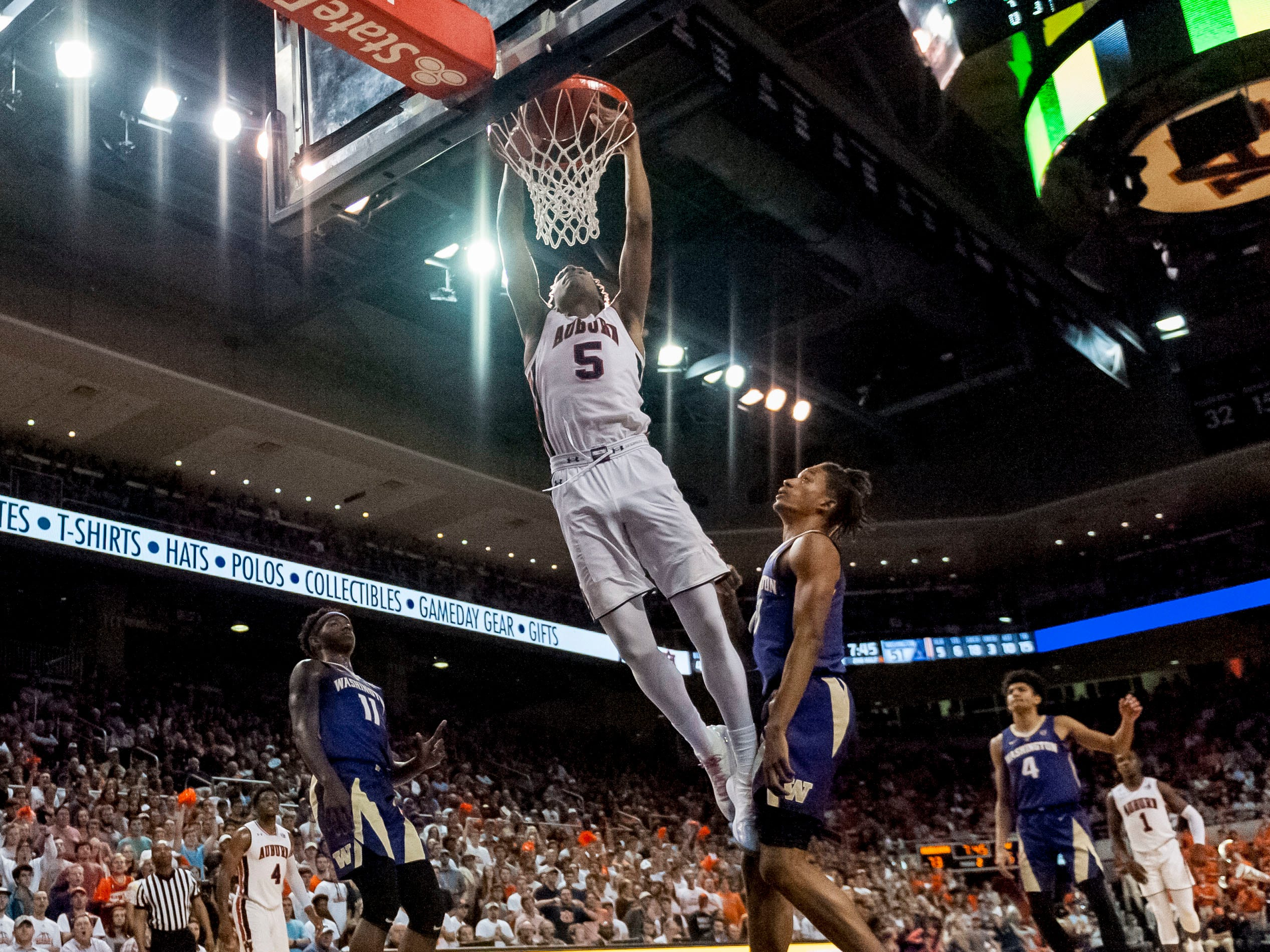 Auburn forward Chuma Okeke (5) dunks between Washington forwards Nahziah Carter (11) and Hamier Wright on Friday, Nov. 9, 2018, in Auburn, Ala.