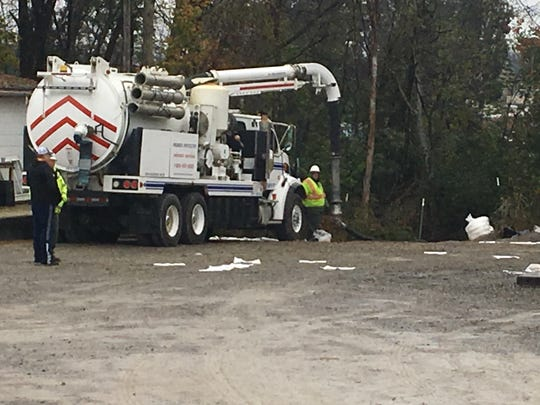 Workers clear an oil spill near Lytle Creek in Murfreesboro on Tuesday.