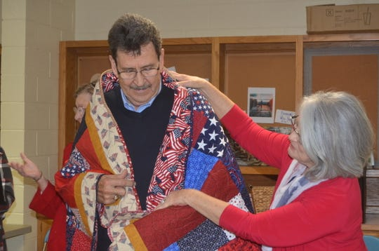 Vietnam War veteran Dan Stepp gets wrapped in a Quilt of Valor by the Lakeshore Quilters Guild in Hendersonville.