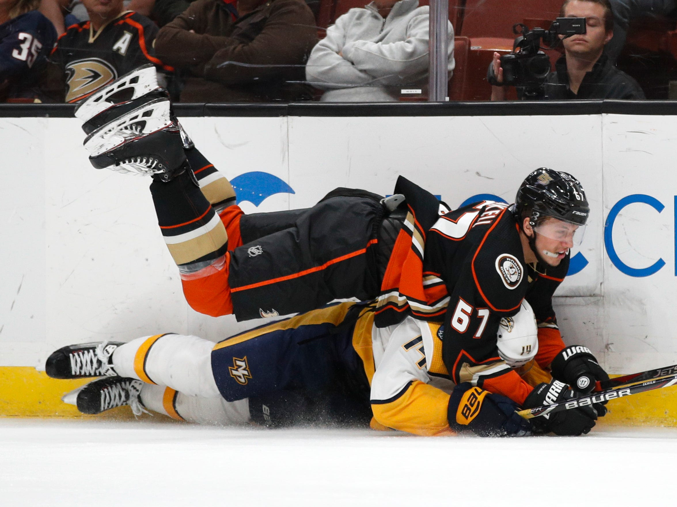 Anaheim Ducks' Rickard Rakell, top, of Sweden, and Nashville Predators' Mattias Ekholm, also of Sweden, fall to the ice as they fight for the puck during the second period of an NHL hockey game, Monday, Nov. 12, 2018, in Anaheim, Calif. (AP Photo/Jae C. Hong)