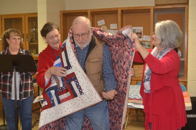 Members of the Lakeshore Quilters Guild wrap Vietnam veteran Don Givens in a Quilt of Valor.