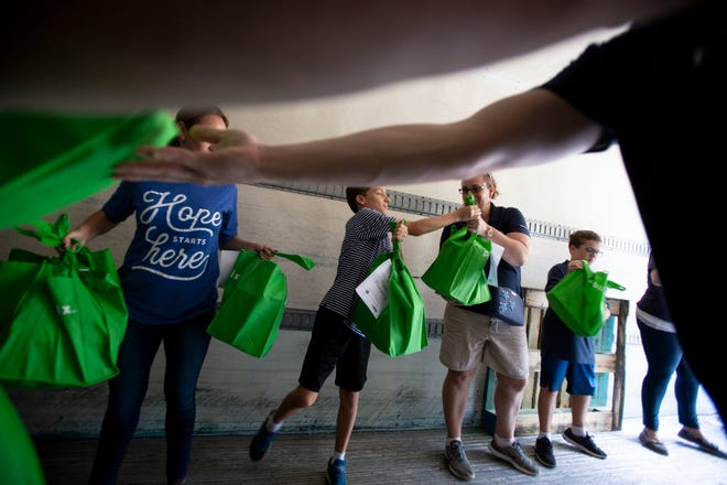 Volunteers move shopping bags filled with donated food in to a refrigerated trailer during the annual Capital Wealth Advisors Turkey Drop, Monday, Nov. 12, 2018 at St. Matthew's House in Naples, Florida.