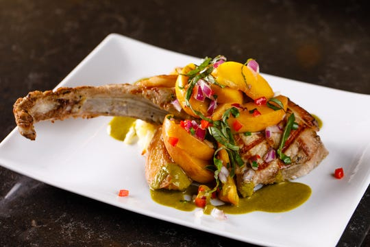 The new Palmetto Creek Farms Single Cut Pork Chop topped with pickled peach salsa and basil verde at The Local restaurant in North Naples.