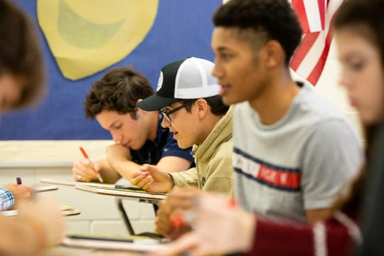 Robert Collins, from second from the left, and Darius Watt, work on an activity for Junior Achievement of the Southwest, Tuesday, Nov. 13, 2018 at Estero High School.