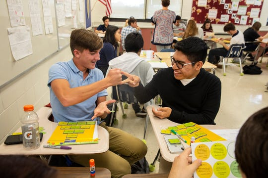 Brandon Adams, left, and classmate Fernando Gonzalez, paper, scissors during a Junior Achievement class project, Tuesday, Nov. 13, 2018 at Estero High School in Estero, Florida.