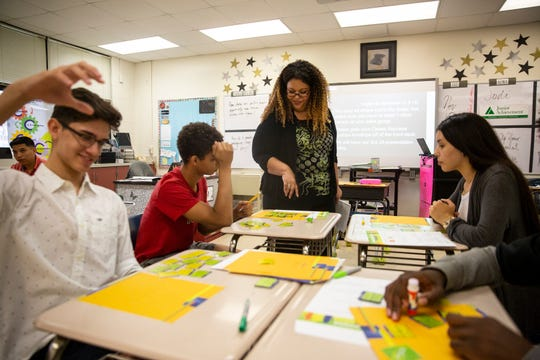 Megan Dixon, an ambassador for Junior Achievement of Southwest Florida, works with a group of Estero High School juniors Tuesday, Nov. 13, 2018 in Estero.