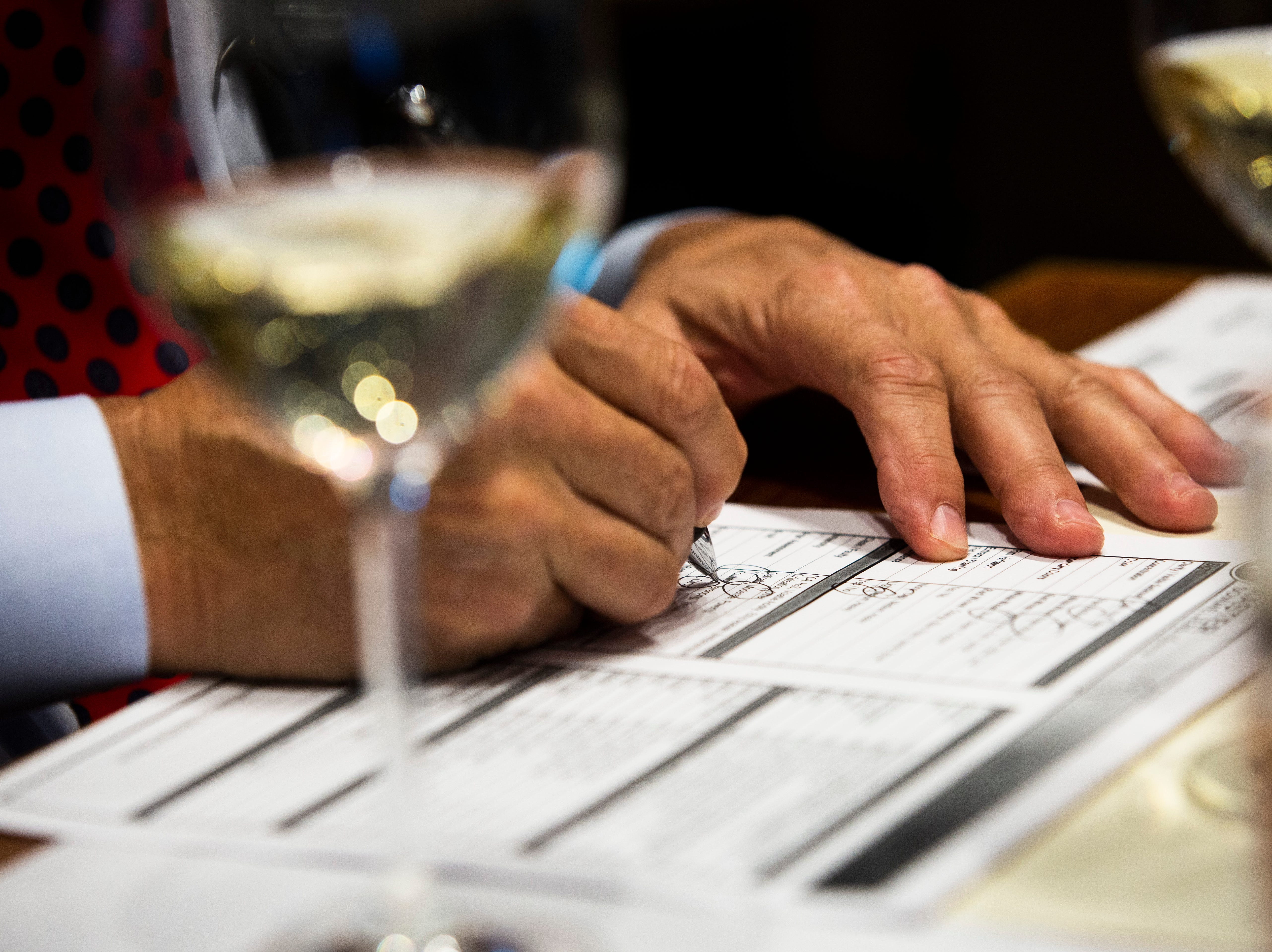 Eric Blais, the wine director and certified sommelier at USS Nemo, writes down his deductions for a blind taste-test of white wine during the Somms Showdown, organized by Break Thru Beverage Group, at The Cave Bistro & Wine Bar in Naples on Tuesday, Nov. 13, 2018.