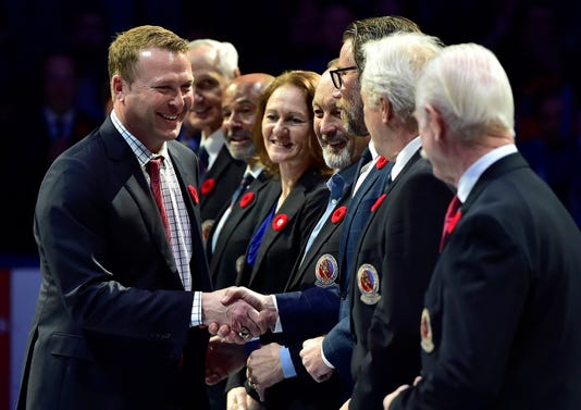 Hockey Hall of Fame inductee Martin Brodeur shakes hands with people associated with the hall.