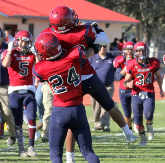 Sophomore Wildcat Jordan Caballero is hoisted high off the ground by senior teammate James Carroll (24) following Caballero's interception that led to a Deming score.