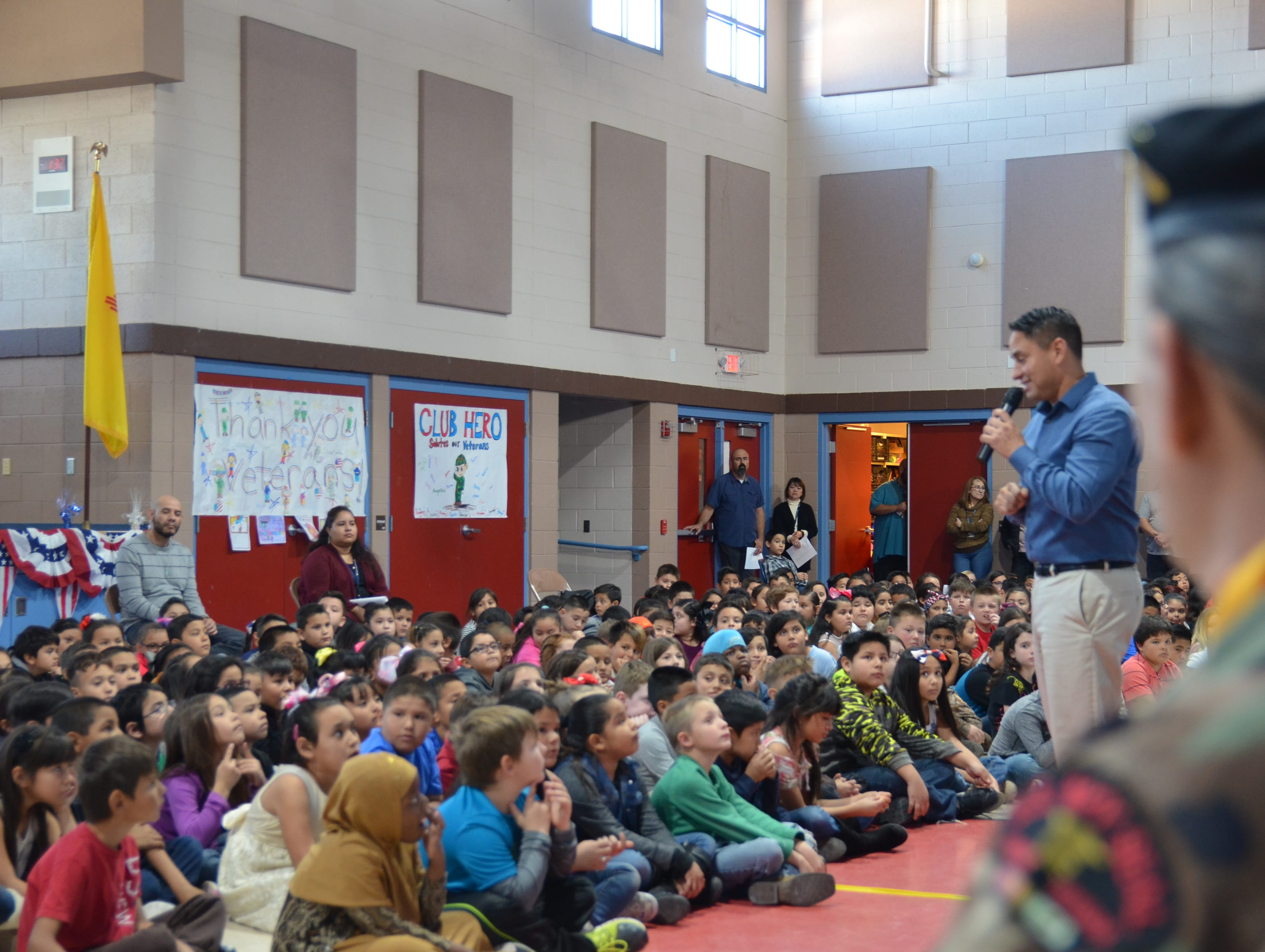 Over the shoulder of Veteran Jose Ray, new elected NM Lt. Gov. speaks to Ruben S. Torres students in honor of Veterans Day.