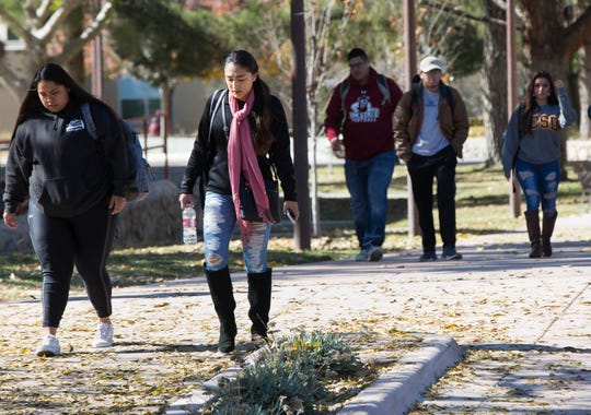 New Mexico State University Students wearing hats, jackets, scarves and gloves walk across campus as a cold snap caused a freeze warning, Tuesday November 13, 2018.