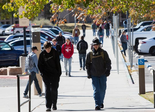 New Mexico State University Students wearing hats, jackets and gloves walk across campus as a cold snap caused a freeze warning, Tuesday November 13, 2018.