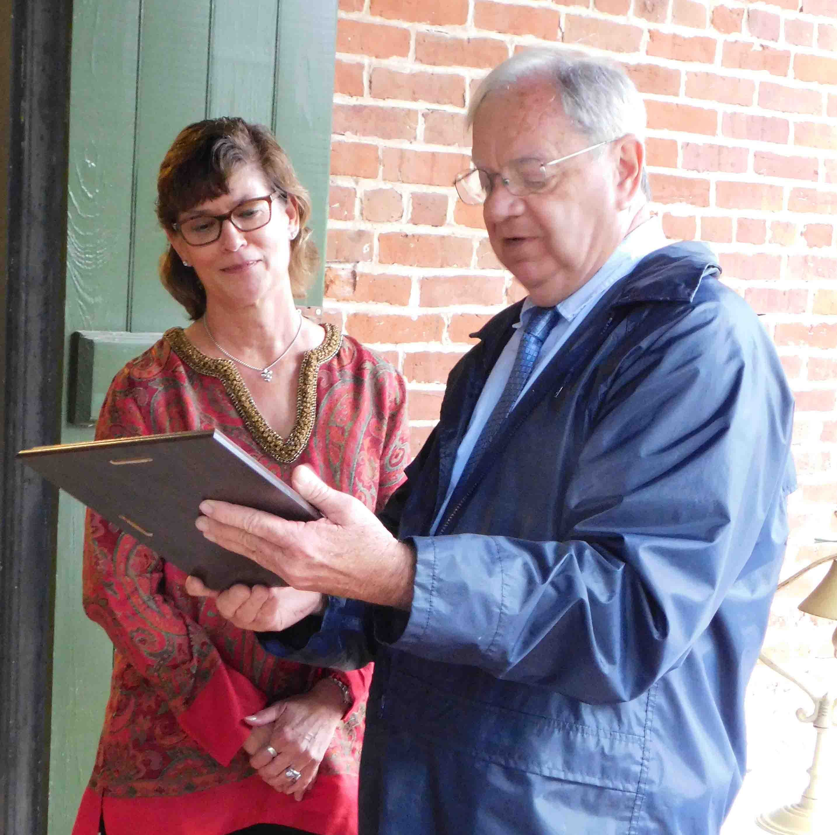 Melissa Robinette accepts the annual Preservationist of the Year award from James Douget, president of the Preservationists of St. Landry, Inc.