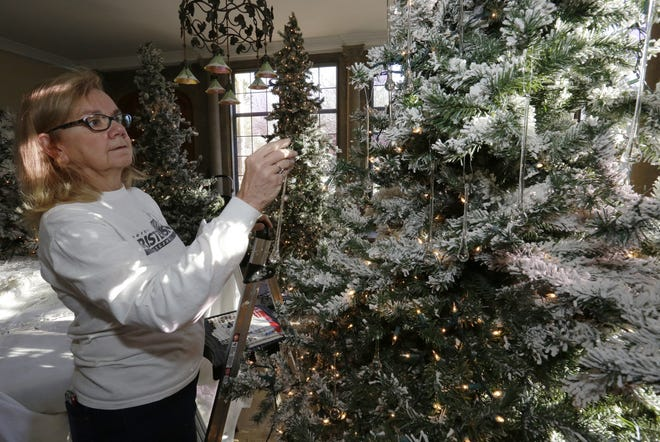 "Linda Christensen hangs glass ornaments on one of the many Christmas trees in the Paine Art Center and Gardens in Oshkosh. ""Nutcracker in the Castle"" will open on Friday and run through January 7."